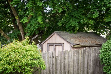 An old shed with a wooden fence in front. Фото со стока