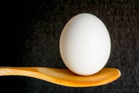 An egg balanced on a wooden spoon.