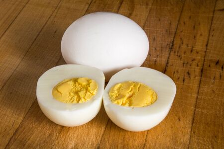 A hard boiled egg on a wooden butcher block.
