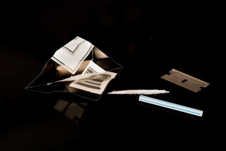Una linea di cocaina su vetro nero. Archivio Fotografico - 90436258