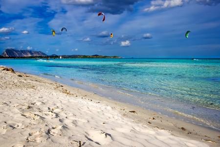 cinta: Kitesurfers gliding at high speed around the beach Cinta, Sardinia