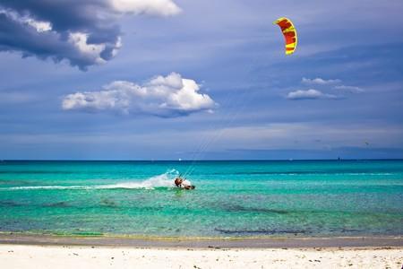 A kitesurfer gliding near the beach La Cinta, Sardinia