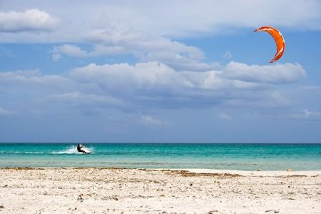 A kitesurfer gliding at high speed around the beach Cinta, Sardinia Stock Photo - 4450752