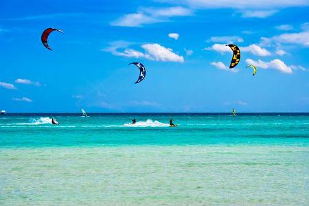 Kitesurfers gliding at high speed around the beach Cinta, Sardinia