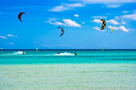 kitesurfen: Kitesurfers glijden op hoge snelheid rond het strand Cinta, Sardinië