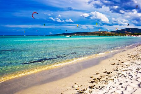 Kitesurfers gliding at high speed around the beach Cinta, Sardinia photo