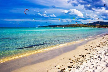 Kitesurfers gliding at high speed around the beach Cinta, Sardinia photo