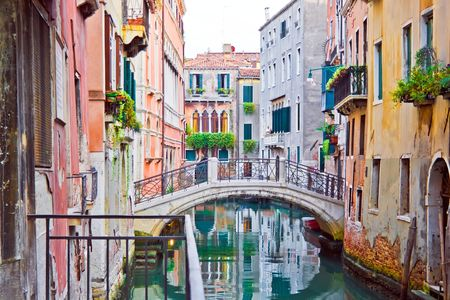 A canal and old white bridge in Venice, Italy