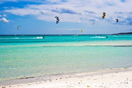 cinta: kitesurfers gliding at high speed around the beach la Cinta, Sardinia