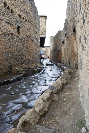 An antique roman street through ruins of Pompeii, Italy photo