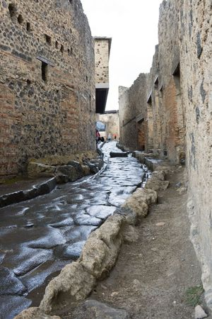 An antique roman street through ruins of Pompeii, Italy
