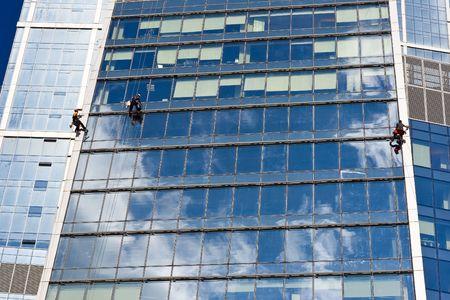 Twee mannen reinigen van ramen van een wolkenkrabber Stockfoto