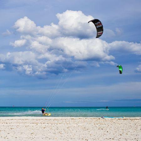 Kitesurfers gliding at high speed around the beach Cinta, Sardinia Stock Photo - 6267145