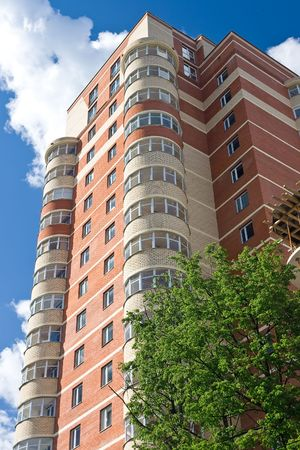 High modern apartment building under blue sky Stock Photo