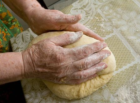 Hands of old woman making dough photo