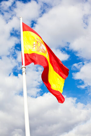 Flag of Spain over blue sky moving in wind photo
