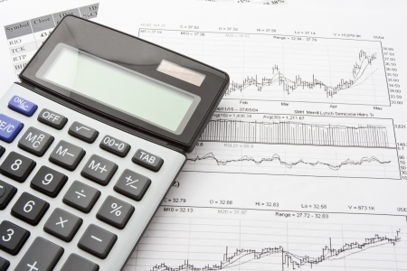 Close-up photo of business objects: calculator and diagrams