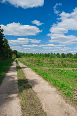 Green meadow and road under blue sky Stock fotó
