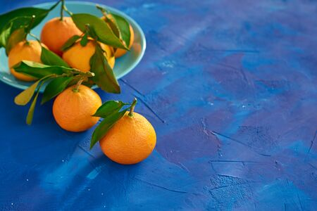 Orange tangerines with leaves on a blue background