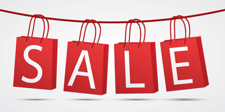 sell out: Realistic red shopping bags hanging on rope with text sale on grey background.