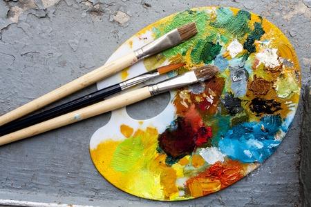 pintor: Cepillos y coloridos colores al óleo abstractas paiters paleta, en el fondo retro Foto de archivo