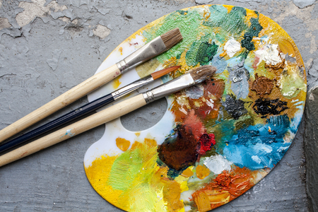Brushes and colorful abstract oil colors paiters pallet, on retro background