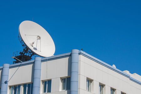 Satellite Dish Antenna on Top of Building, Blue Sky Background.
