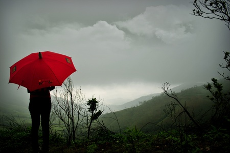 monsoon clouds: Girl standing in rain in western ghats