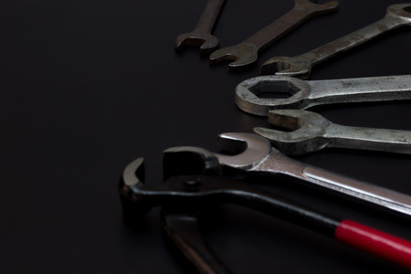 Wire cutters, pliers and wrench. Low key Tools on darkness background.