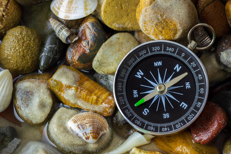 Compass on the pebbles and shell at riverside. Concepts of tourism and adventure.