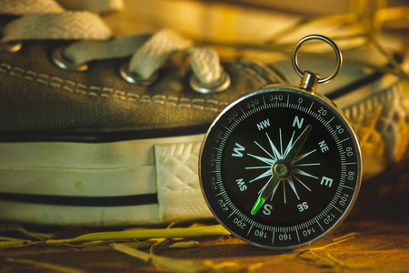 Compass and sneakers with pine flowers and dry wheat straw on wooden table in morning sunlight. Concept of adventure tourism or survival in the forest.