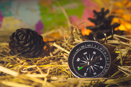 Compass with paper maps and pine flowers placed on dry wheat straw in morning sunlight. Concept of adventure tourism or survival in the forest.