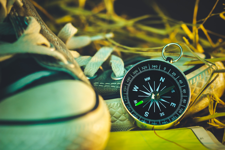 Compass and paper maps with sneakers and pine flowers placed on dry wheat straw in morning sunlight. Concept of adventure tourism or survival in the forest.