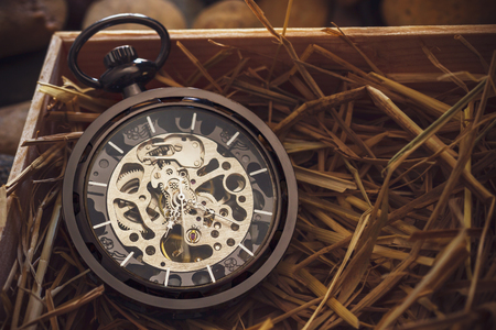 Pocket watch winder on natural wheat straw in a wooden box. Concept of vintage or retro gift.