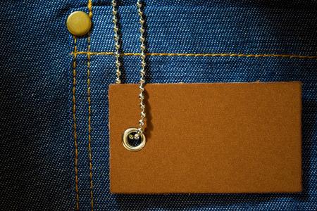 Lederetikett des Produktpreises und Kugelkette aus Edelstahl auf Jeanskleidung. Das Konzept der Fashion-Jeans.