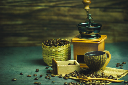 Brew black coffee in coconut cup and morning lighting. Roasted coffee beans in a bamboo basket and wooden spoon. Vintage coffee grinder and moka pot. Concept of coffee time in morning or start the new day.