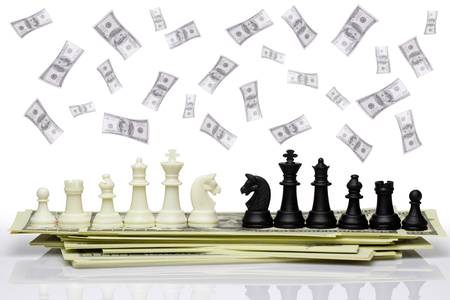 Chess face each other on a dollar banknote and dollar is falling from the top. Concept of business strategy or business war. Isolate on white background with clipping path.