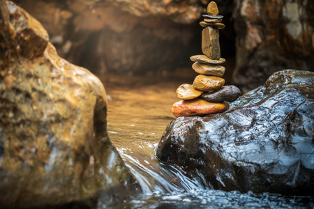 Stone balance stacking at riverside and morning sunlight. Concepts of Concepts of Zen religion or meditation practice.