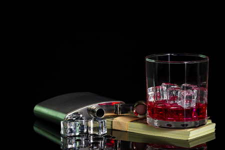 Stainless steel flask liquor alcohol and ice on table with glass on dollar banknote in darkness background. Copy space for text or articles. Stock Photo