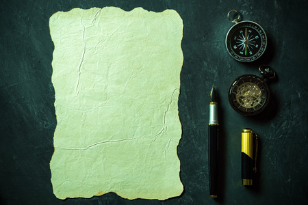 Vintage paper and pen with compass and pocket watch on black background. Top view and copy space for text.