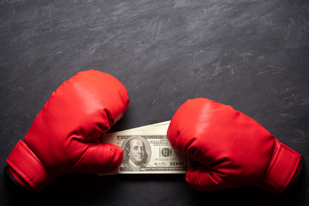 Boxing Gloves holds the dollar banknote on black cement background. Concept of boxing betting or business struggle. Top view and copy space for text.