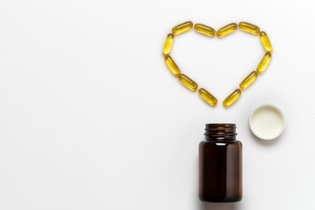 Fish oil capsule is arranged into the heart shape on white background. Concept of healthy care. Top view and copy space for text.