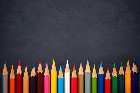 Crayons de couleur sur fond de tableau. Vue de dessus et espace de copie. Concept d'éducation artistique.