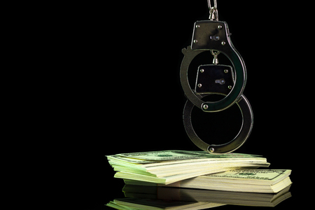 Handcuffs were hung on a dollar banknote in darkness background. Copy space for text or articles. Concept of cheating or corruption. Editorial