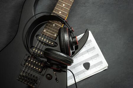 Black electric guitar and Headphone on black cement floor. Top view and copy space for text. Concept of rock music. Imagens - 132061191