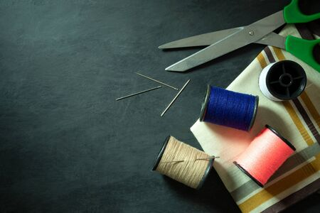Sewing tools and equipment on black cement floor. Top view and copy space for text. Concept of tailor or fashion designer. Imagens