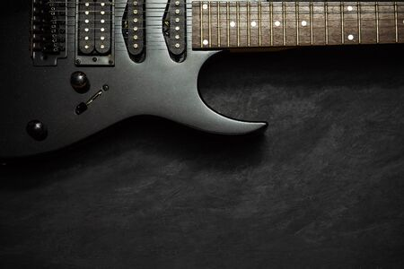 Black electric guitar on black cement floor. Top view and copy space for text. Concept of rock music.