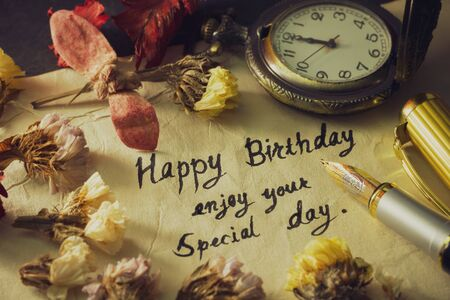 Happy birthday enjoy your special day. Vintage brass pen writing birthday greetings on old paper. Decoration by pocket watch and dry flower around it. Imagens