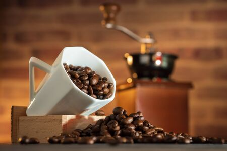 Coffee bean in the white cup and coffee grinder on wooden table. Concept breakfast or coffee time in morning. Imagens