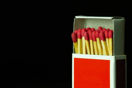 Matches stick in red paper box on black background. Closeup and copy space.